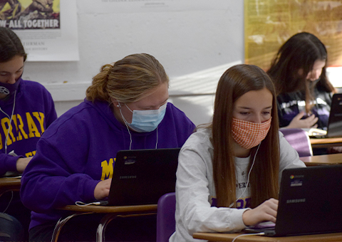 Students wearing mask work on laptops