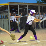 Softball player hitting ball with team in background