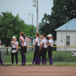 Softball team in huddle by fence in outfield