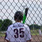 Boy in batters box with back to the fence number 35