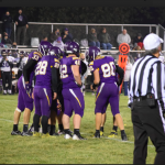 Football players on field in huddle with referee close by