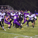 Football players on field with other team in the middle of a play