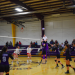 Girls on volleyball court with one setting the ball