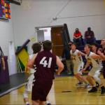 Boys basketball players playing defense under basket