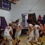 Boys basketball players playing offense