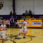 Boys basketball players running down the court