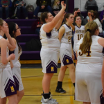 Hannah shooting basketball with team mates around her