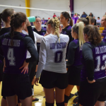 Girls HS volleyball team in a huddle