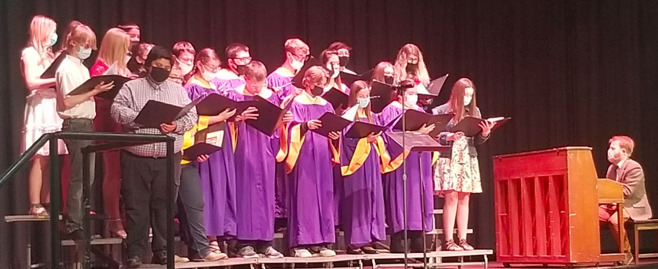 High School Choir singing while Mr. Calahan plays piano